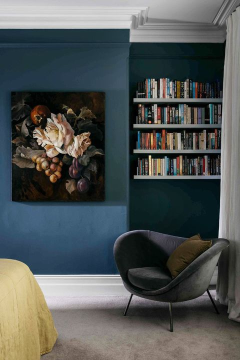 bedroom with dark blue walls and floating shelves