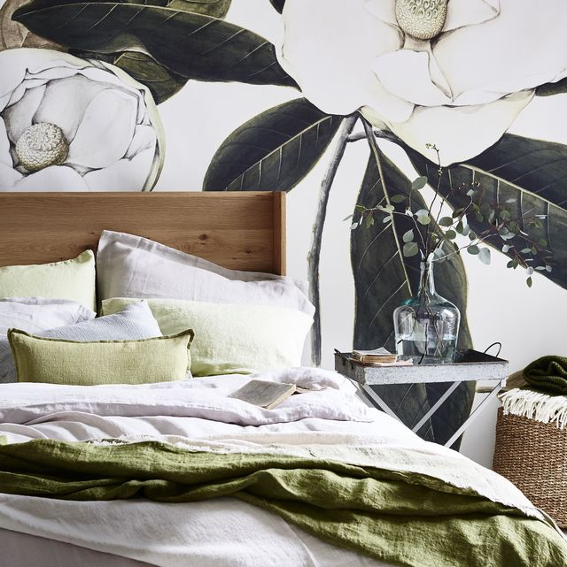 calming bedroom scheme, a bedroom with a large white and green flower on the wallpaper, a bed made with green and white sheets, and a side table with a large glass vase with green stalks in it