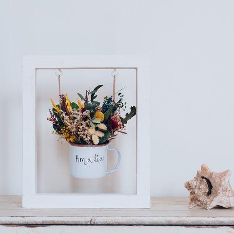 Centro de flores preservadas en una taza personalizada