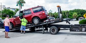 Florida, Vero Beach, flatbed tow truck with red SUV