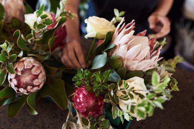 florist making a flower arrangement with proteas