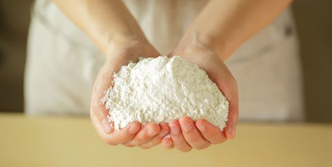 Flour on palm of young woman,close up