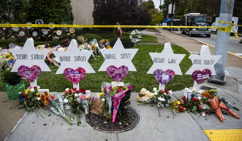 Flowers and stones are placed on the memorials erected...