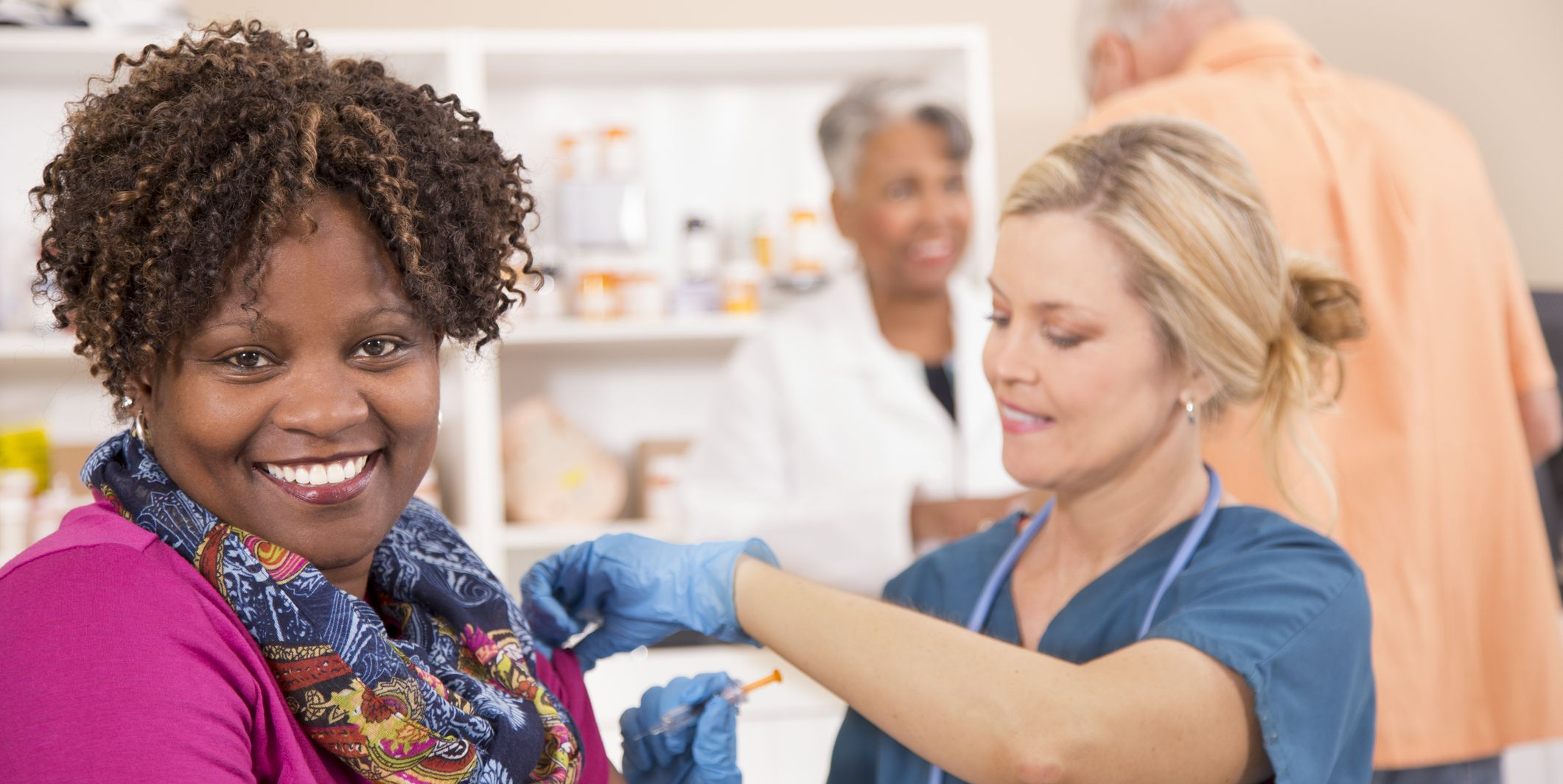 Nurse gives flu shot vaccine to patient at pharmacy.