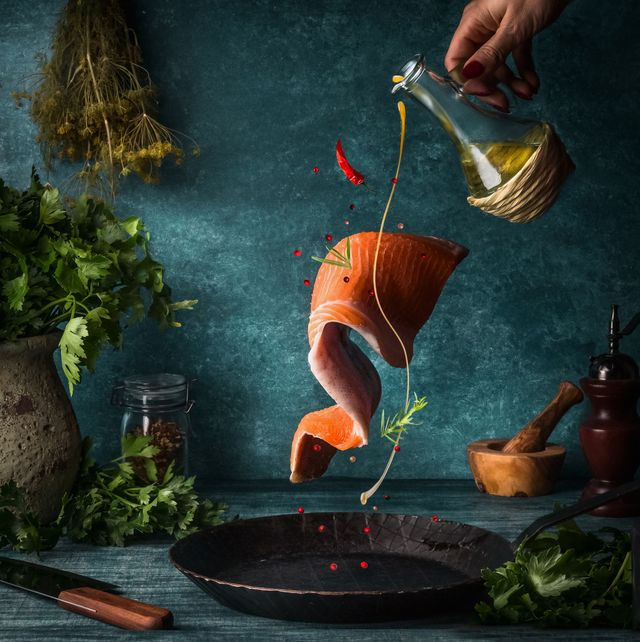 flying salmon fillet with herbs, spices and female hand with pouring olives oil