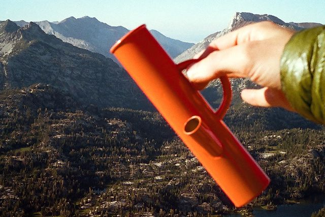 a hand holding an orange bong against a mountain backdrop