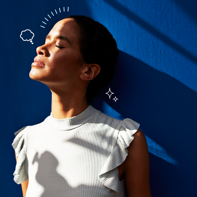 a woman standing against a blue wall with closed eyes looking toward the sun