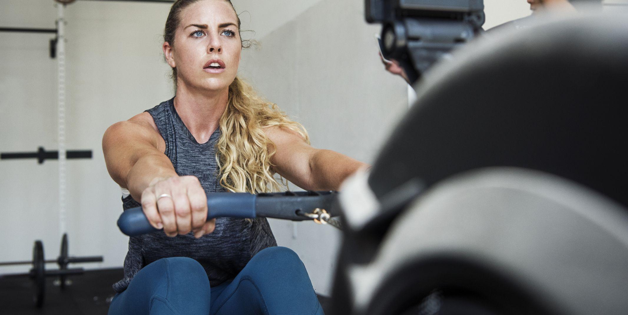 Focused athlete exercising on rowing machine in crossfit gym