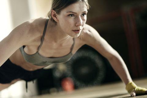 Focused female boxer doing push-ups