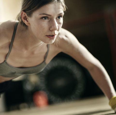 focused female boxer doing pushups