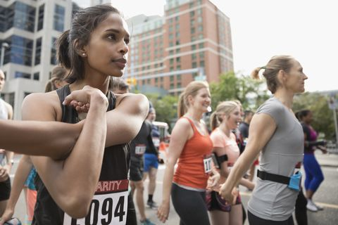 Focused female runner stretching arm on urban street