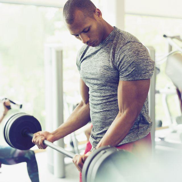Homme concentré faisant des biceps avec haltères dans la salle de gym