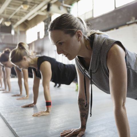 Focused, strong women exercising, doing planks in a row in exercise class