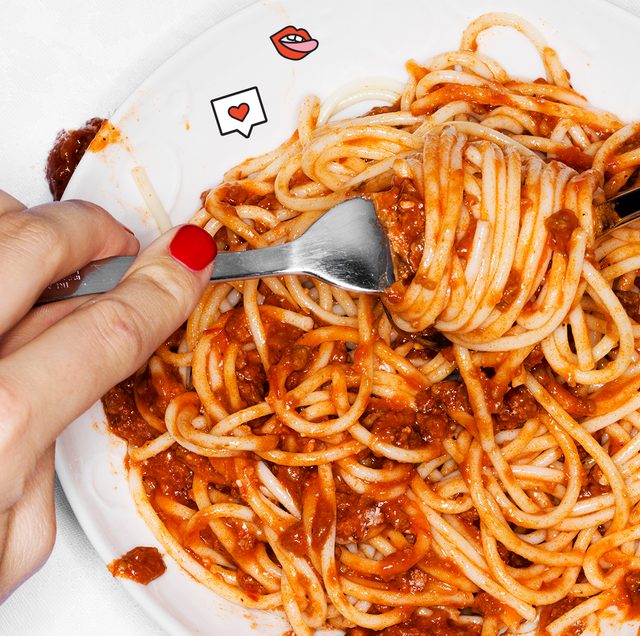 a person with red nails eating a bowl of spaghetti with meat sauce