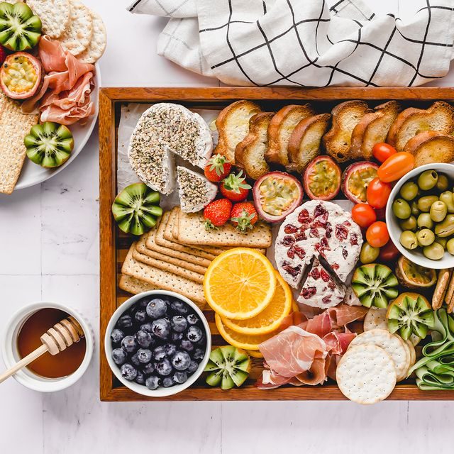 cheese fruit cracker olives on wooden tray