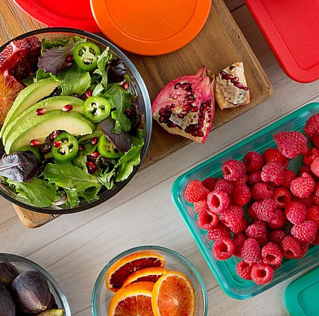 food storage containers with salad and cut fruit in them