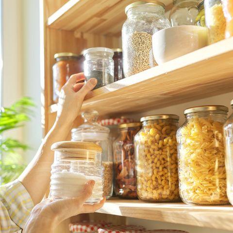 food storage in pantry, woman holding jar of sugar in hand