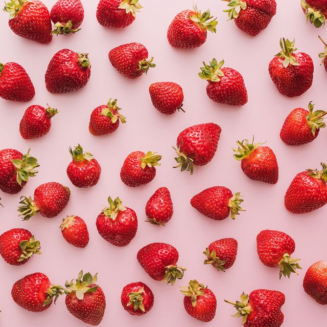 top view of whole and red strawberries on white background