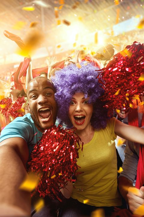 biggrinon the foreground a group of cheering fans watch a sport championship on stadium a man doing a selfie with his girlfriend a girl is happy and everybody are happy people are dressed in casual cloth colourful confetti flies int the air