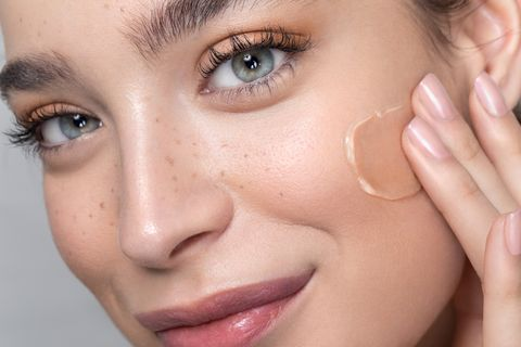 Young woman with perfect skin applying foundation
