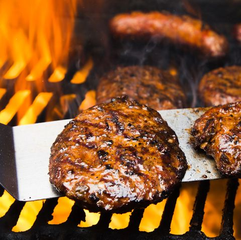 Four Beef Burgers and Two Bratwursts on a hot Barbeque Grill