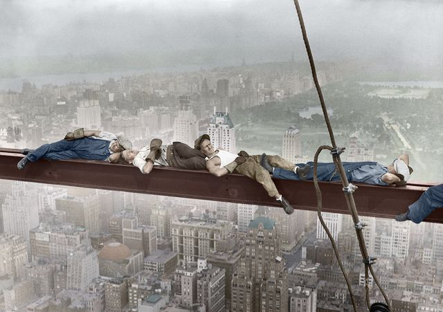 construction workers resting on steel beam above manhattan