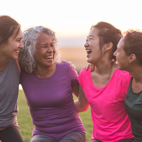 Four ethnic women laughing together after an outdoor workout
