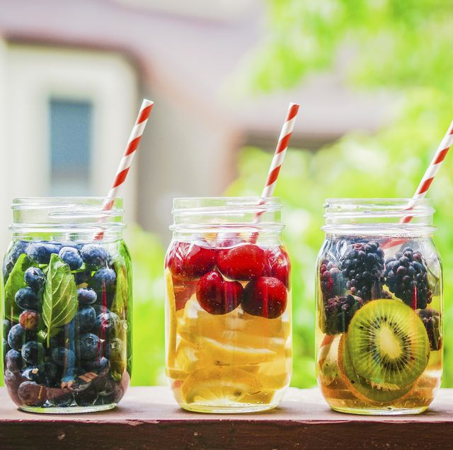 four fruity drinks in screw top jars on a garden table