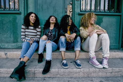 Four young women with curly hair sitting side by side on steps outside a building.