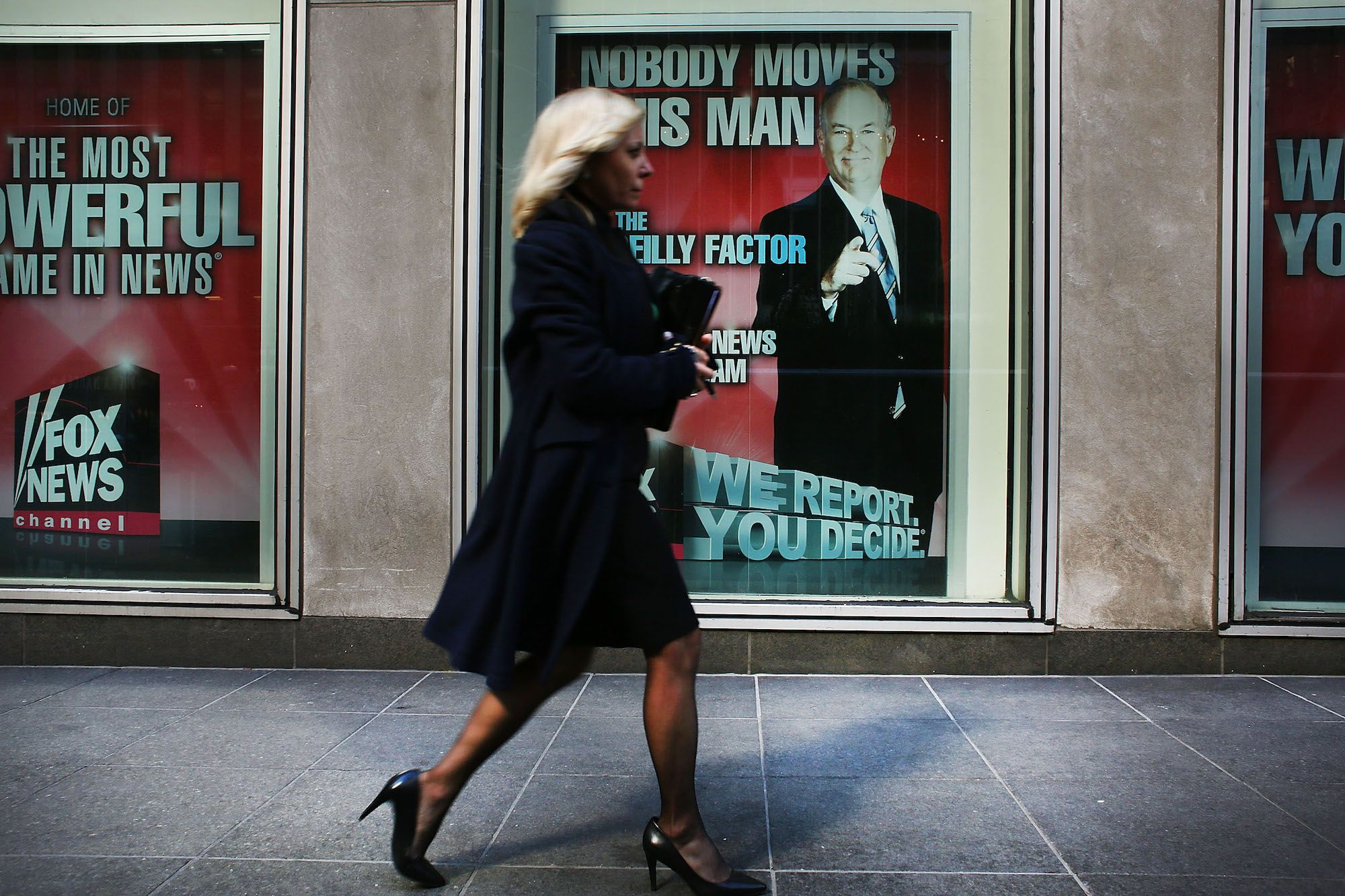 A woman strides by a poster of Bill O'Reilly outside Fox News headquarters in April 2017.