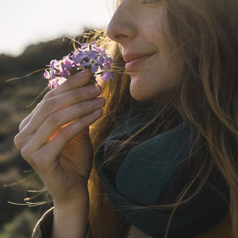 Woman enjoying fragrance of a flower