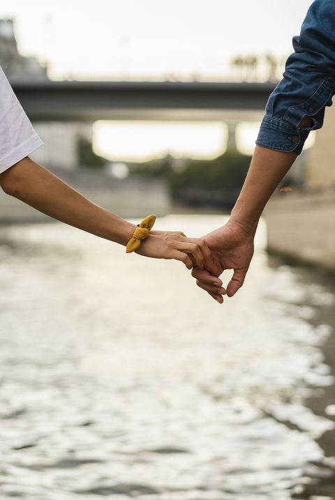 France, Paris, couple holding hands at river Seine