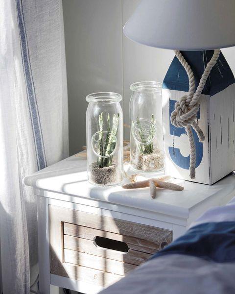 cactus en frascos de cristal en la mesita de noche