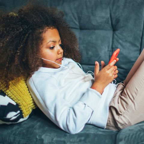 girl on couch with headphones and phone