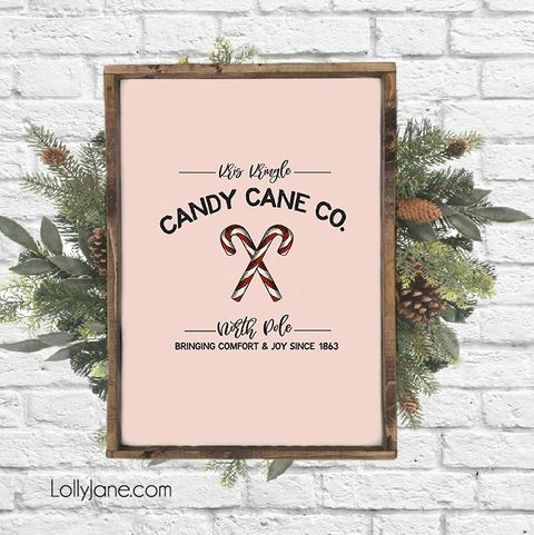 a pink sign that says kris kringle candy cane co with two crossed candy canes in the middle