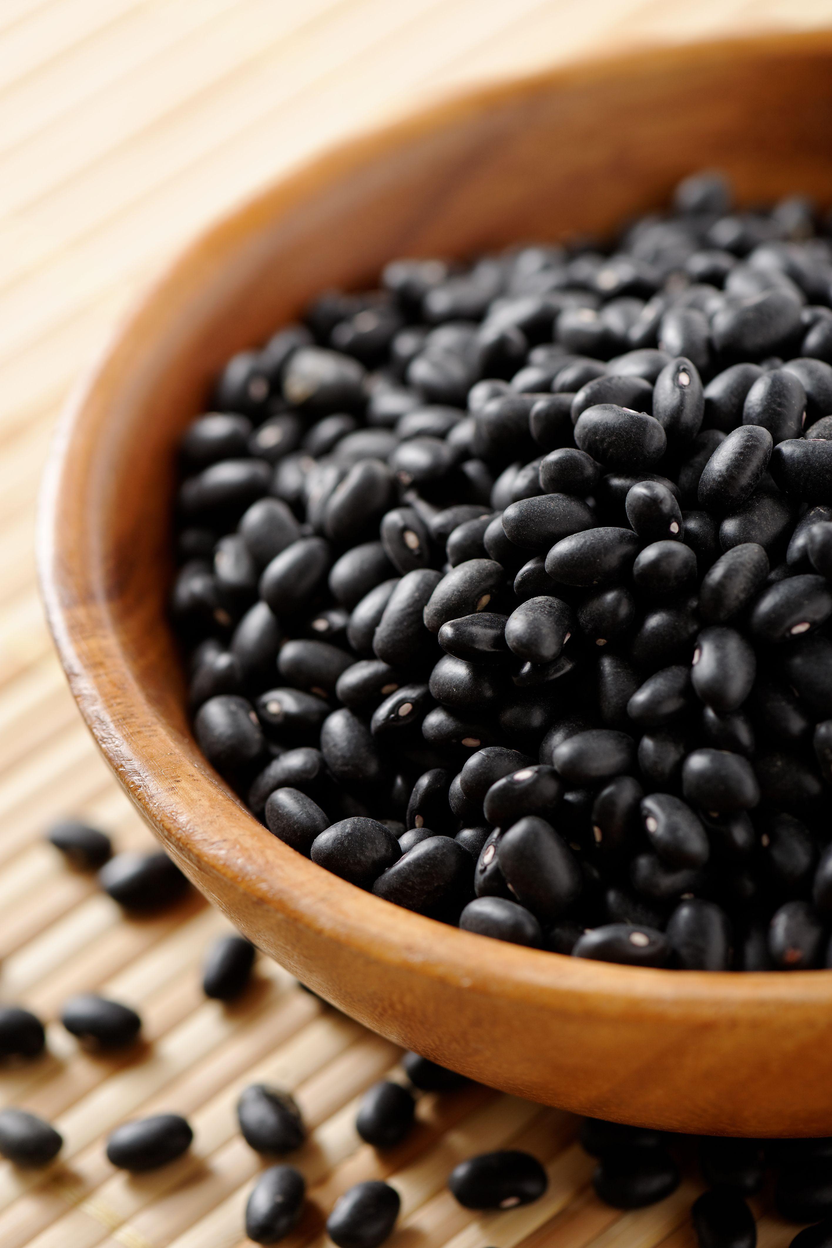 Fresh black beans in wooden bowl
