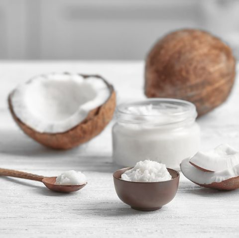 Fresh coconut oil and nuts on wooden table