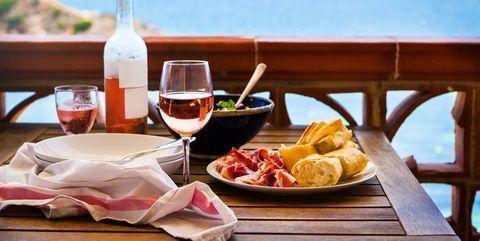 fresh delicious dinner   salad, bread, ham, rose wine on balcony