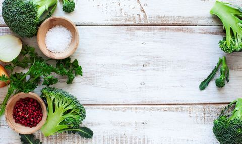 Fresh green broccoli, parsley, onion, salt and red pepper on wooden background.