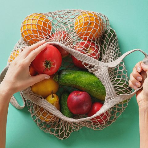 fresh juicy fruits and vegetables, products in a reusable shopping bag a girl or woman takes or lays out products from a string bag made from recycled materials on a green pastel background vegetarianism, veganism no plastic