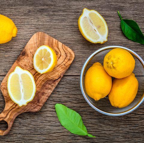 Fresh lemons and  lemons leaves on rustic wooden background.