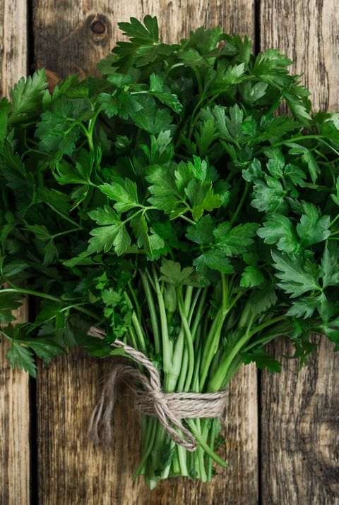 Fresh organic parsley over wooden background