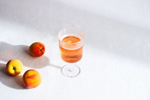 fresh peaches fruit  and  glass of fruity cold lemonade summer drinks concept minimal still life with shadows