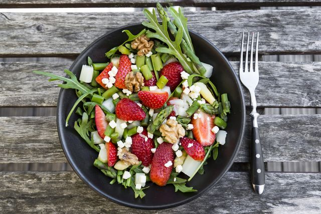 fresh salad of asparagus, strawberries, rocket, feta cheese and walnuts