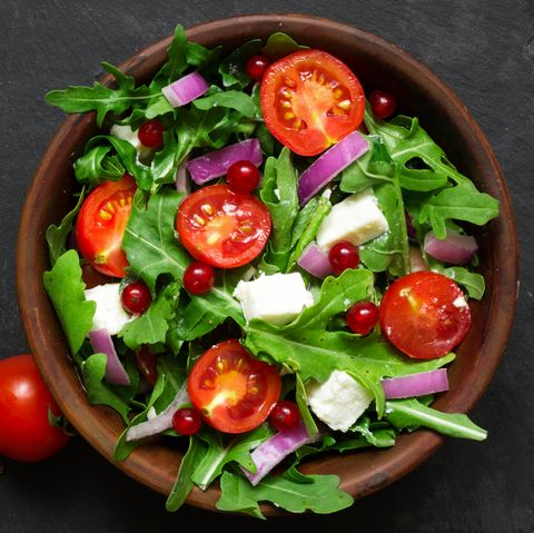 Fresh salad with arugula, feta cheese, red onion and red currant in a bowl