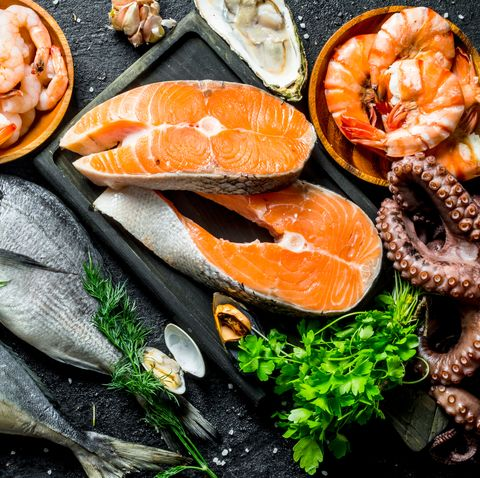 fresh salmon steak with a variety of seafood and herbs