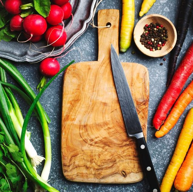 fresh spring vegetables around wooden cutting board with kitchen knife for vegetarian cooking, top view