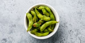 Fresh steamed Edamame soybean pod with spice on concrete background