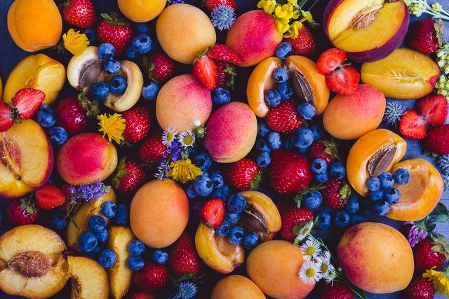 frutta estiva colorata, pesche, albicocche e frutti di bosco