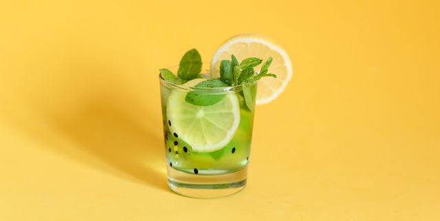 fresh summer fruits water or lemonade with lemon, orange and mint on yellow background close up